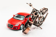 A motorcycle and a red color car model Stock Photos