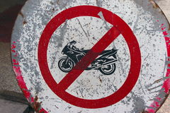 Motorcycle restriction sign. A closeup view of an old, battered and beaten sign restricting the use of motorcycles Stock Photos