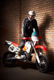 Motorcycle rider. Standing on unkempt enduro motorcycle on the outskirts of the city at night Stock Photography