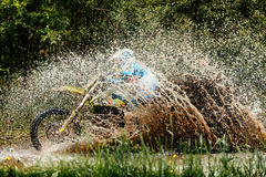 Motorcycle rider crosses puddle. Splashes of water and dirt Royalty Free Stock Photography