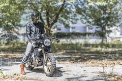 Motorcycle rider on custom made scrambler style cafe racer in th. Cool looking motorcycle rider on custom made scrambler style cafe racer in the park stock photography