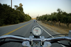 Motorcycle rider and cyclists. Motorcycle moving on a straight road from rider's perspective with cyclists ahead royalty free stock image