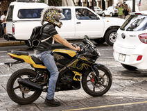 Motorcycle rider with decorative helmet. A motorcycle rider with a decorative helmet rides down a city street in mid day traffic Stock Photography