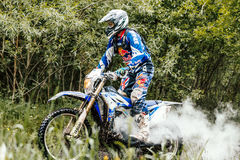 Motorcycle rider in forest of exhaust gas back Stock Photography