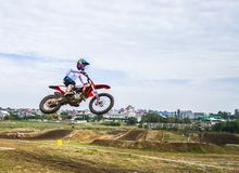 A motorcycle rider participates in a motocross race. Jumps on the trampoline. Royalty Free Stock Photo