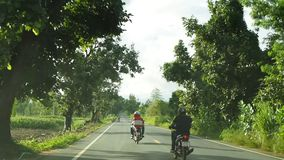 Motorcycle riders overtake a car on a small road in Thailand. PAK THONG CHAI, NAKHON RATCHASIMA, THAILAND -OCTOBER 11, 2015: A group of unidentified motorcycle stock video