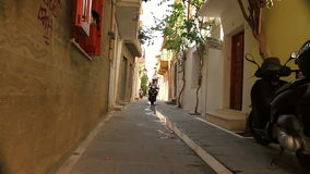 Motorcycle rides along the street of a small ancient village stock footage