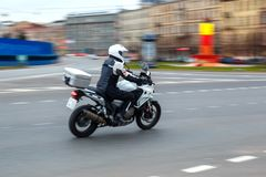 Motorcycle rides with speed on city roads stock photography