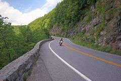 Motorcycle riding down curvy road. Royalty Free Stock Photo