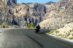 Motorcycle riding in mountains. A motorcycle riding up the road to red rock canyon in Nevada Royalty Free Stock Photos