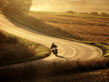 Motorcycle on the road at autumn evening Royalty Free Stock Images