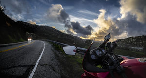 Motorcycle on a Road at Sunset. Red street bike motorcycle looking at a cloudy sunset on an open road scenic route. The vehicle is cropped to be generic and non stock photos