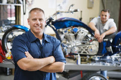Motorcycle Shop. Portrait of a confident mechanic with coworker at motorcycle shop stock photography
