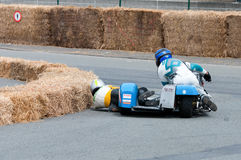 Motorcycle Sidecar race in Ostend Belgium. The assistant is shaving the ground and almost hitting the hay bales in a curb Royalty Free Stock Photo
