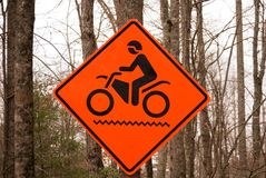 Motorcycle sign. Sign on a dirt road to alert drivers to beware Stock Photos