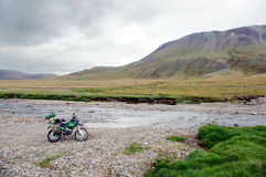 Motorcycle single traveler with suitcases standing on stone bank of mountain river stream Royalty Free Stock Image