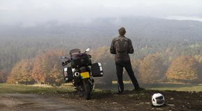 Motorcycle and standing rider in an autumn valley. Royalty Free Stock Photos
