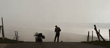 Motorcycle and standing rider silhouetted against a misty valley. Stock Images