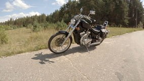 Motorcycle stands on the roadside stock footage