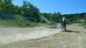 Motorcycle starts the movement. Wheel of motocross bike starting to spin and kicking up ground or dirt. Slow motion