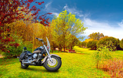 Motorcycle. Striking view of a motorcycle standing in a beautiful park under a blue cloudy sky Stock Image