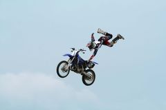 Motorcycle Stunt. A person performing a trick on a motorcycle, shot against a blue sky Stock Images