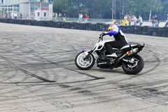 Motorcycle stunt drifting on dirty asphalt. This motorcycle stunt rider is drifting on dirty asphalt, near tire wall on racing circuit Royalty Free Stock Photo