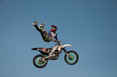 Motorcycle stunt man. A professional motorcycle rider performs stunts in a mid air jump Stock Images