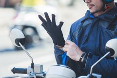 Motorcycle taxi driver wearing his gloves for safety riding royalty free stock photo