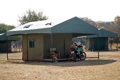 Motorcycle at a tent in a campground in Pilanesberg National Park. Motorcycle parked in front of a permanent tent in a campground in Pilanesberg National Park stock photography