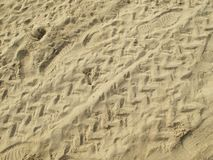 Motorcycle Trails and Human Footprints on a Sandy Beach stock photography