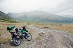 Motorcycle traveler with suitcases standing on extreme rocky road in a mountain valley in cloudy weather Stock Photography