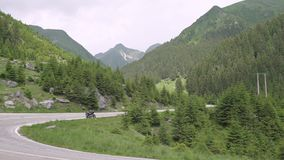 Motorcycle of traveler on the Transfagarasan highway in Romania, the most beautiful road in Europe. Motorcycle of traveler on the Transfagarasan highway in stock video footage