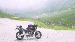 Motorcycle of traveler on the Transfagarasan highway in Romania, the most beautiful road in Europe. Motorcycle of traveler on the Transfagarasan highway in stock footage
