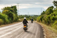 Motorcycle travels on the National Highway T 16 from Salavan to Pakse. Asphalt road on Bolaven Plateau at evening, Laos people royalty free stock photography