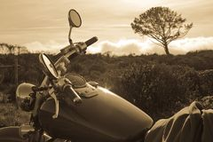 Motorcycle and Tree. Sepia toned image of a motorcycle and single tree in the background Royalty Free Stock Images