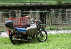 Motorcycle with Trunk. Singapore - July 2016 A motorcycle with a trunk attached parked next to a canal royalty free stock photography