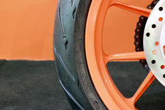 Motorcycle Tyre and Rim. Motorcycle Tyre and Orange Rim Closeup On the Floor Royalty Free Stock Image