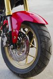 Motorcycle wheels parked in a road. Closeup view of wheel royalty free stock image