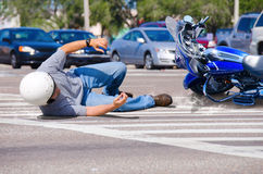 Motorcycle wreck at a busy intersection. Motorcycle rider has wrecked and is laying in the road as his motorcycle goes sliding into the busy intersection Stock Photos
