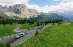 Motorcycles and cars traveling through a sharp turn of a highway winding at the foothills of rugged Sella stock photos