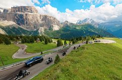 Motorcycles and cars traveling through a sharp turn of a highway winding at the foothills of rugged Sella stock photography