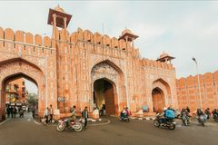 Motorcycles driving past Ajmer gate of historical city wall and moving vehicles of Rajasthan. JAIPUR, INDIA - JAN 24, 2016: Motorcycles driving past Ajmer gate Royalty Free Stock Images