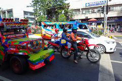 Motorcycles and Jeepney Traffic in Cebu City. Cebu City, Philippines - January 15, 2015: Bikers wait at traffic light with cars and iconic jeepneys during stock images