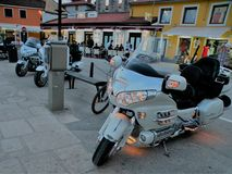 Motorcycles with lighted lights stand in line with stones paved in the coastal town of Croatia, right next to the Adriatic Sea.In royalty free stock photo