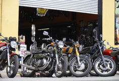 Motorcycles outside a workshop. Various motorbikes parked at the curb outside a workshop garage Stock Images