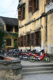 Motorcycles are parked along a building (Vietnam) Royalty Free Stock Photos