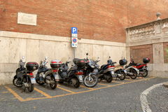Motorcycles parked in a row near the old wall Royalty Free Stock Images