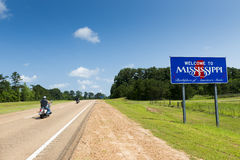 Motorcycles passing by the Mississippi State welcome sign along the US Highway 61. Two motorcycles passing by the Mississippi State welcome sign along the US royalty free stock image