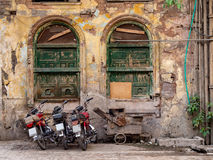 Motorcycles and wooden cart Peshawar Pakistan. Motorbikes and cart standing in front of derelict building in Peshawar, Pakistan Stock Image